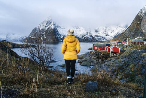 Tourist enjoying the view at Hamnoy, Lofoten, Norway - DGOF00101