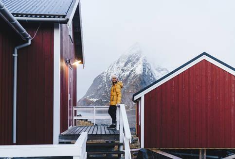 Tourist on a porch at Hamnoy, Lofoten, Norway - DGOF00110