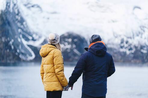 Tourist couple enjoying the view at Hamnoy, Lofoten, Norway - DGOF00140