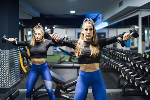 Twin sisters exercising with dumbbells in gym - OCMF00993