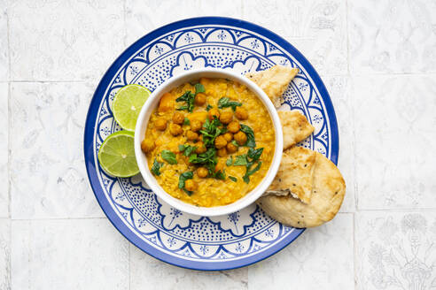 Vegan lentil curry with red lentils, sweet potatoes, spinach, roasted turmeric, chickpeas, with lime juice and coriander and naan bread - LVF08577