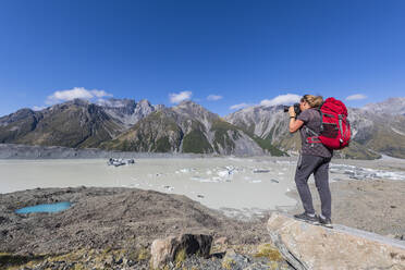 New Zealand, Oceania, South Island, Canterbury, Ben Ohau, Southern Alps (New Zealand Alps), Mount Cook National Park, Tasman Glacier Viewpoint, Woman photographing Tasman Lake with ice floes - FOF11625