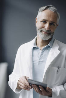 Portrait of smiling doctor with digital tablet - KNSF07355