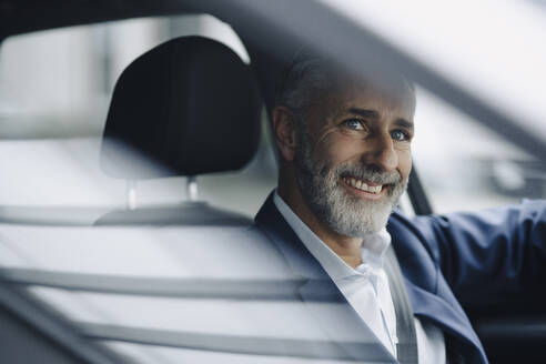 Portrait of smiling mature businessman in his car - KNSF07373