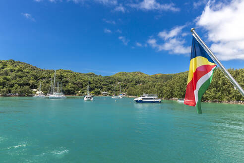 Seychelles, Praslin Island, Flag of Seychelles with marina in background - MABF00547