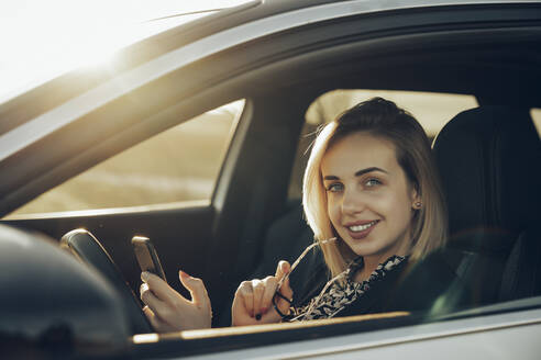 Portrait of smiling young woman with smartphone sitting in her car in the evening - MTBF00340
