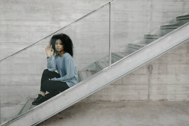 Beautiful young woman sitting on stairs behind a glass pane - TCEF00098