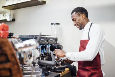 Smiling barista preparing a coffee in a coffee shop - OCMF01013