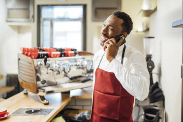 Happy barista on the phone in a coffee shop - OCMF01022
