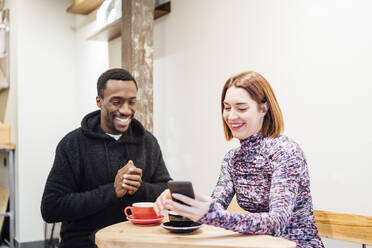 Smiling man and woman with cell phone in a cafe - OCMF01025