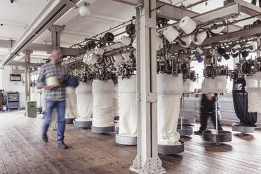 Blurred view of man walking in a textile factory - SDAHF00065