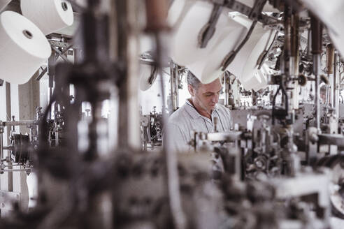 Man working at a machine in a textile factory - SDAHF00068