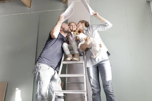 Parents on construction site at home kissing daughter on ladder - KMKF01219