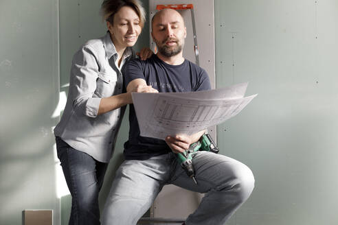 Couple on construction site at home studying plan - KMKF01222
