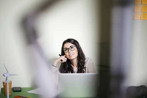 Young woman sitting at desk in office thinking - JRFF04042