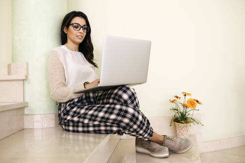 Young woman sitting on stairs using laptop - JRFF04069