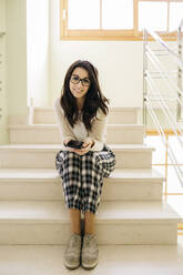 Portrait of smiling young woman sitting on stairs holding cell phone - JRFF04075