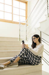 Young woman sitting on stairs using cell phone - JRFF04078