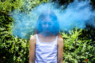 Portrait of girl behind blue powder paint cloud - SARF04456