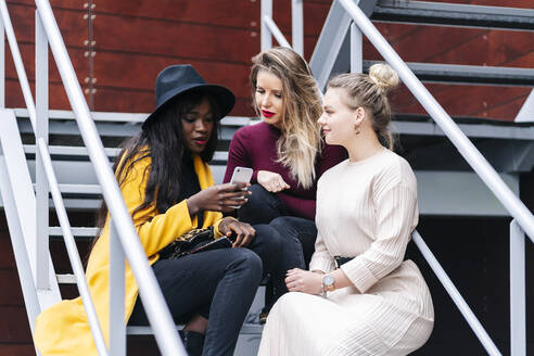 Girlfriends sitting on stairs outdoors looking at mobile phone - DGOF00173