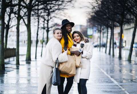 Portrait of happy girlfriends in the city on a rainy day - DGOF00194