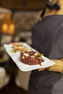 Waitress serving steak tartar on white plate - VABF02569