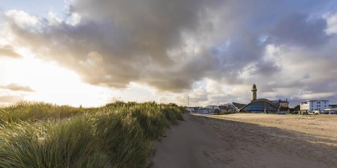 Germany, Mecklenburg-West Pomerania, Warnemunde, Grass on sand dunes and lighthouse at sunset - WDF05731