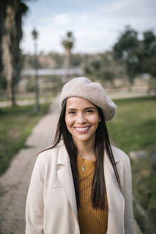 Portrait of smiling young woman with beret in a park - GRCF00143