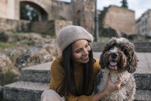 Happy young woman stroking her dog in the city - GRCF00146