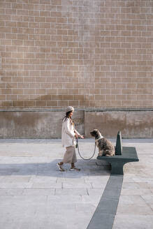 Young woman with her dog in the city on a bench - GRCF00149