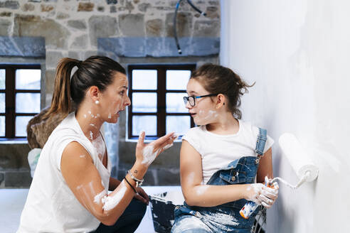 Mother arguing with her daughter while painting a wall of her new house - DGOF00222