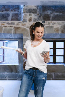 Woman using her cell phone while painting the walls of her new house - DGOF00243