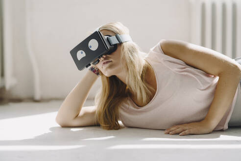 Young woman lying on the floor wearing VR glasses with squinting eyes - KNSF07401