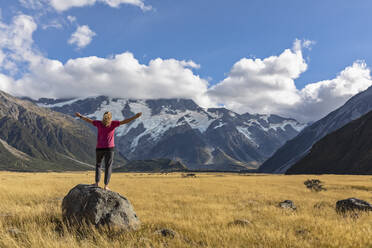 New Zealand, Oceania, South Island, Canterbury, Ben Ohau, Southern Alps (New Zealand Alps), Mount Cook National Park, Aoraki / Mount Cook, Woman standing on boulder in mountain landscape - FOF11658
