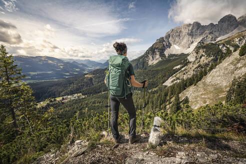 Woman on a hiking trip at Wilder Kaiser enjoying the view, Kaiser mountains, Tyrol, Austria - MSUF00164