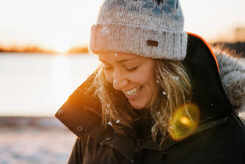 Portrait of woman laughing with snow in her hair in winter at sunset - CAVF73737