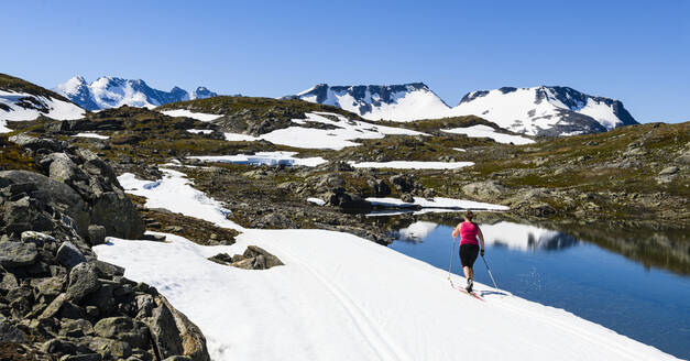 Woman cross-country skiing in mountains - JOHF06714
