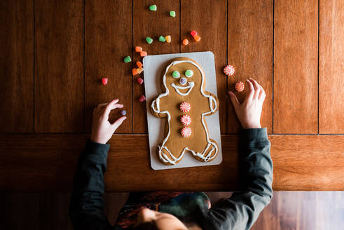Small kid decorating a gingerbread man on the kitchen table - CAVF73871