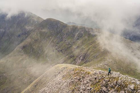 Hiker walking down rocky mountain ridge - CAVF73985