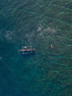 Aerial view of surfers and boat in the ocean - CAVF74106