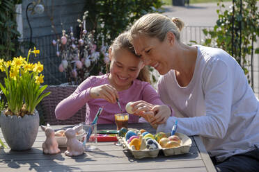 Happy mother and daughter sitting at garden table painting Easter eggs - LBF02861