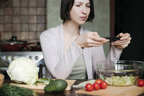 Portrait of woman taking photo of salad with smartphone - EYAF00912