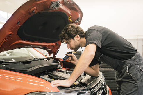Car mechanic in a workshop working at car - MOEF02752