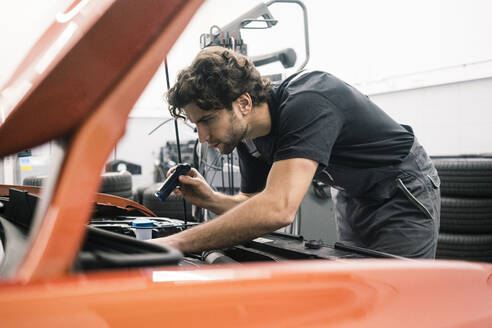 Car mechanic in a workshop working at car - MOEF02767
