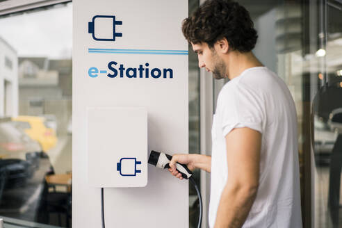 Man charging an electric car at a station - MOEF02794