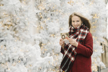 Portrait of smiling young woman standing on the street with Christmas card in front of white Christmas trees - AHSF01842