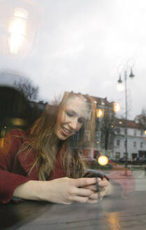 Portrait of smiling young woman using mobile phone in a coffee shop - AHSF01848