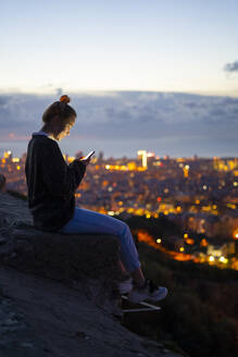 Young woman sitting on railing above the city using cell phone, Barcelona, Spain - GIOF07942
