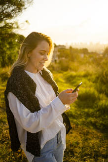 Smiling young woman using cell phone at sunrise in nature - GIOF07948