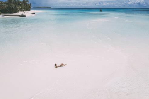 Woman lying on a sandbank in the sea, Maguhdhuvaa Island, Gaafu Dhaalu Atoll, Maldives - DAWF01218